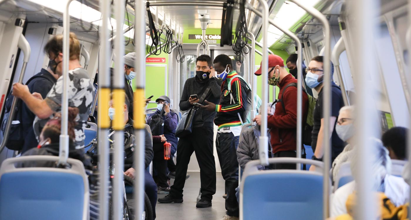 Passengers wearing masks inside of a BART train