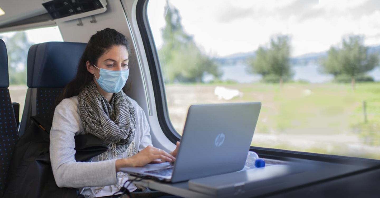 Mujer con mascarilla usando el transporte público mientras trabaja en su computadora